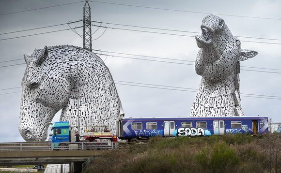 The Class 314 car passenger train passes through the Kelpies sculpture in Falkirk on its way to the workshop in Bo'ness | Credit: Arcola