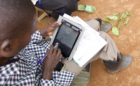 Ugandan coffee farmer using his tablet computer | Credit: Rainforest Alliance
